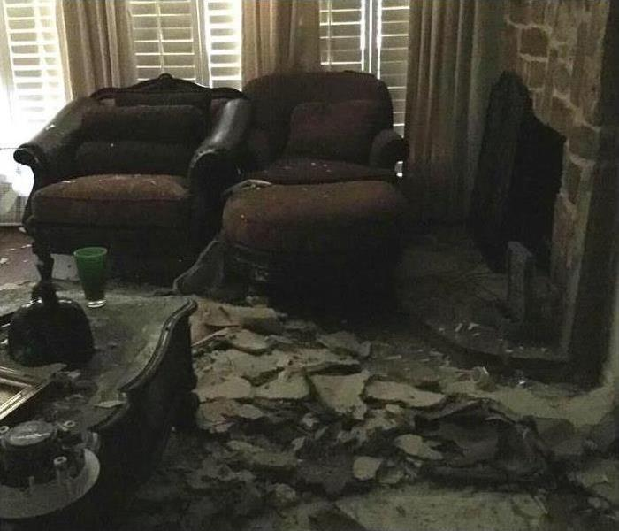 furniture covered in rubble from a collapsed ceiling caused by a burst water heater