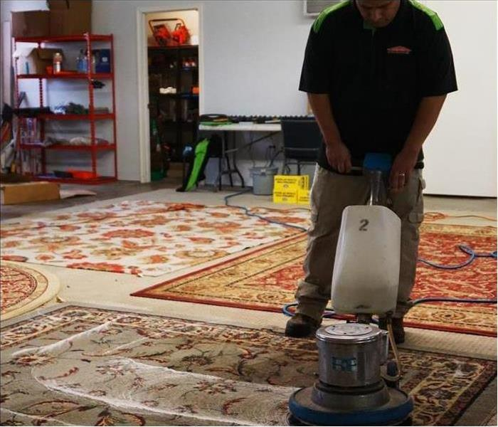 employee using a carpet cleaner to clean rugs laid out on the floor